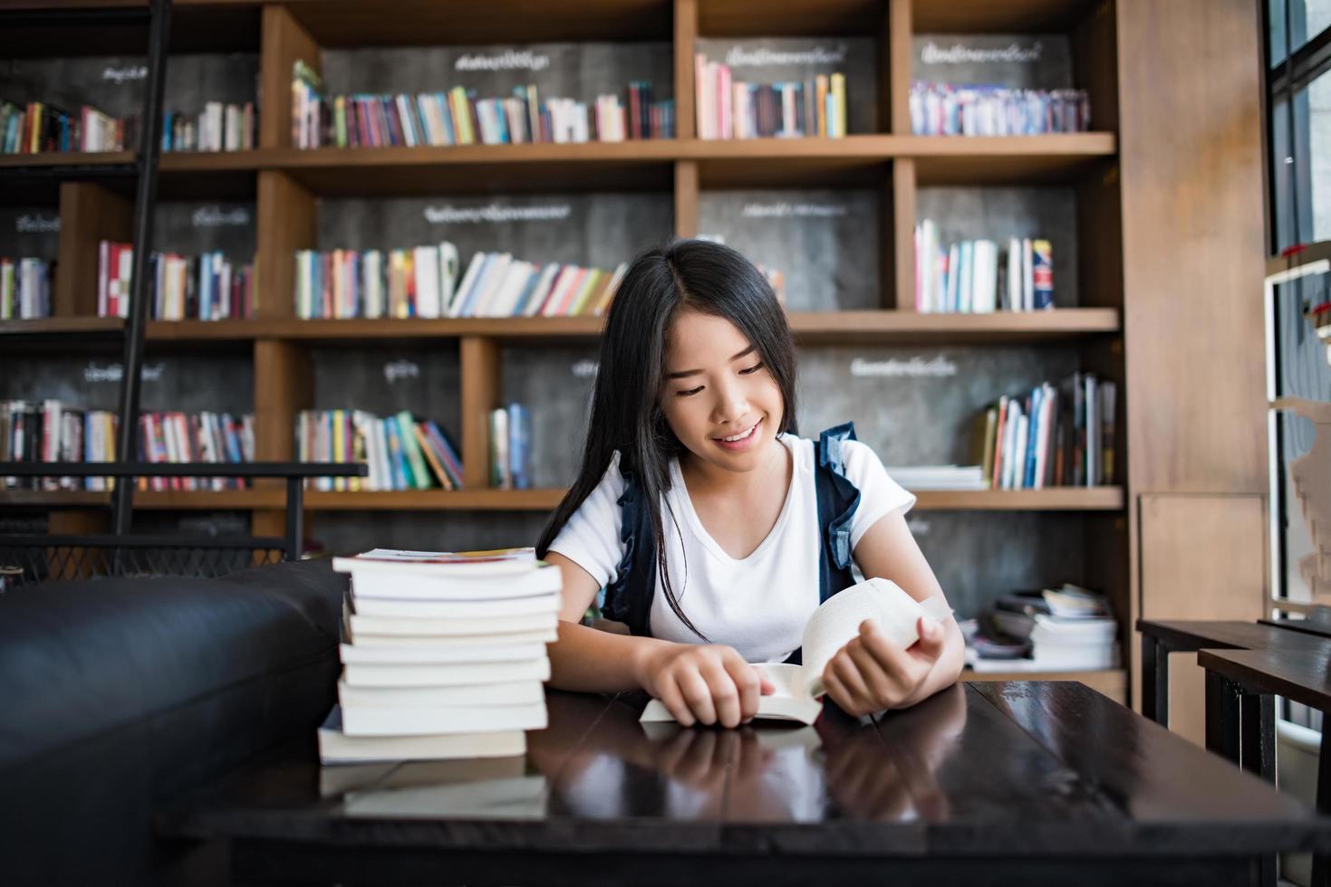 jonge vrouw lezen van een boek zitten in deuren in stedelijk café foto