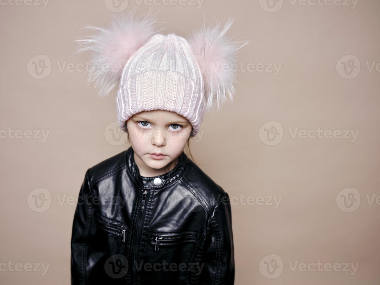 portret van een mooi klein meisje met een wollen hoed en een leren jas foto