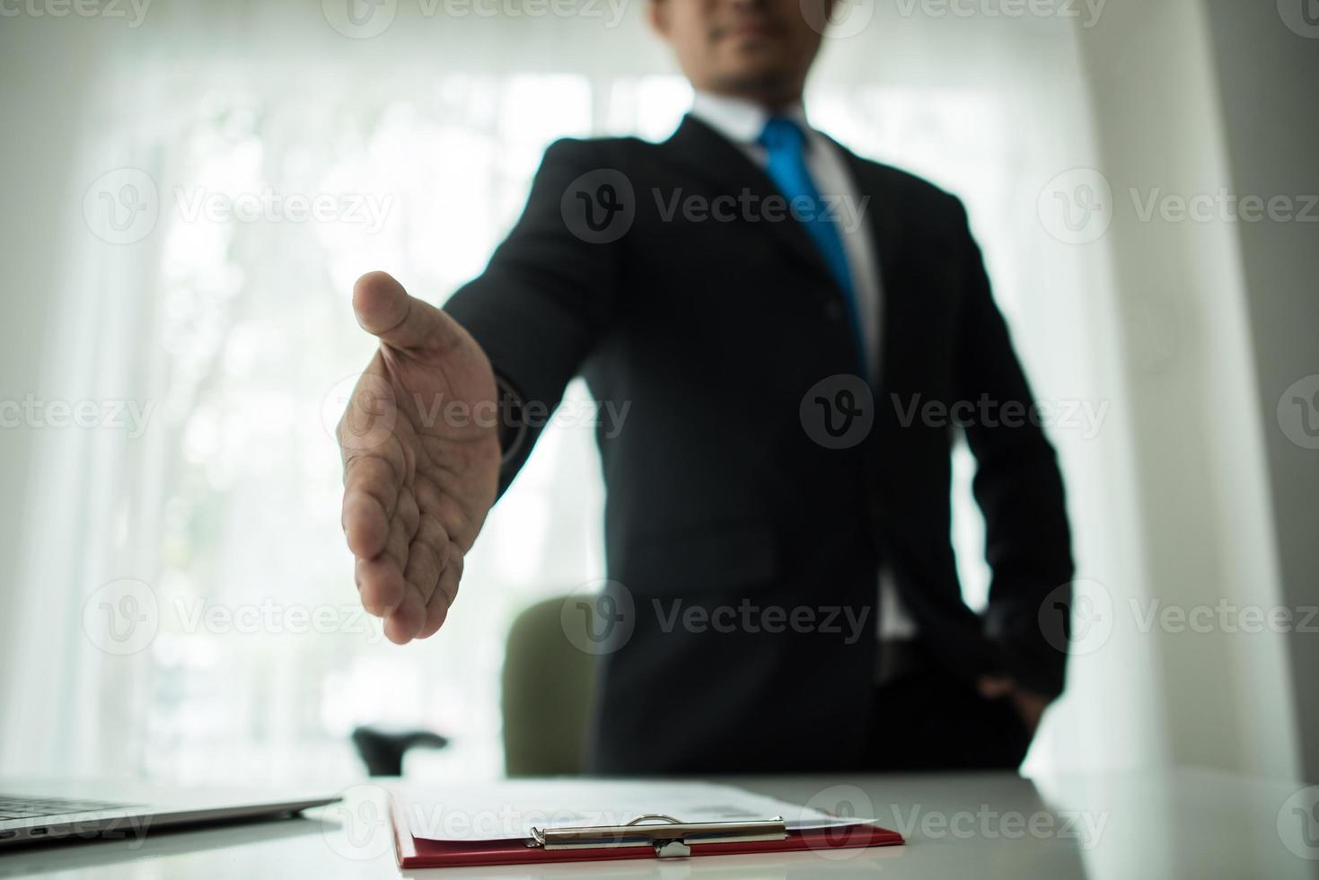 jonge zakenman een handdruk te verlengen foto