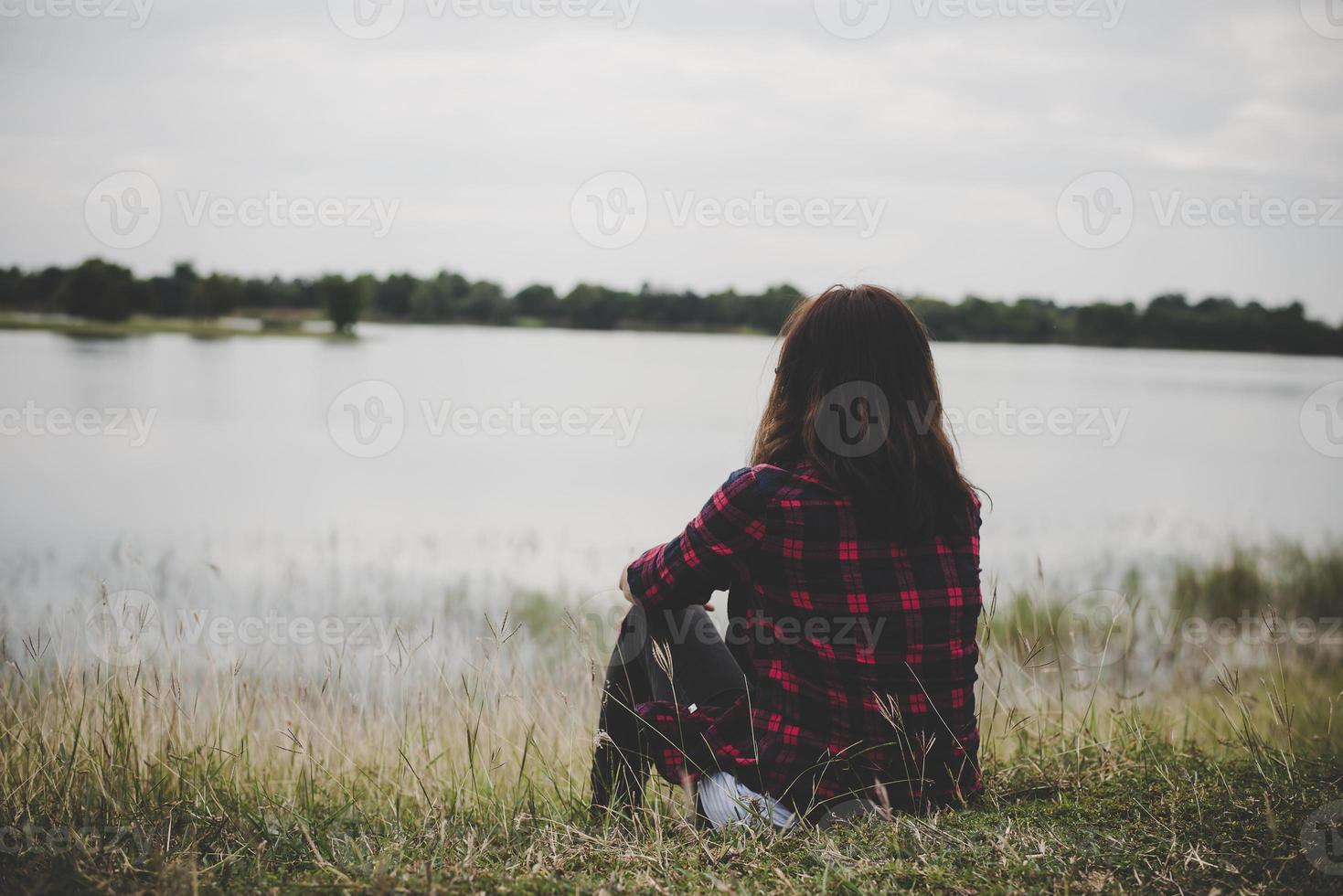 jonge hipster vrouw zittend op het gras in de buurt van het meer ontspannen foto