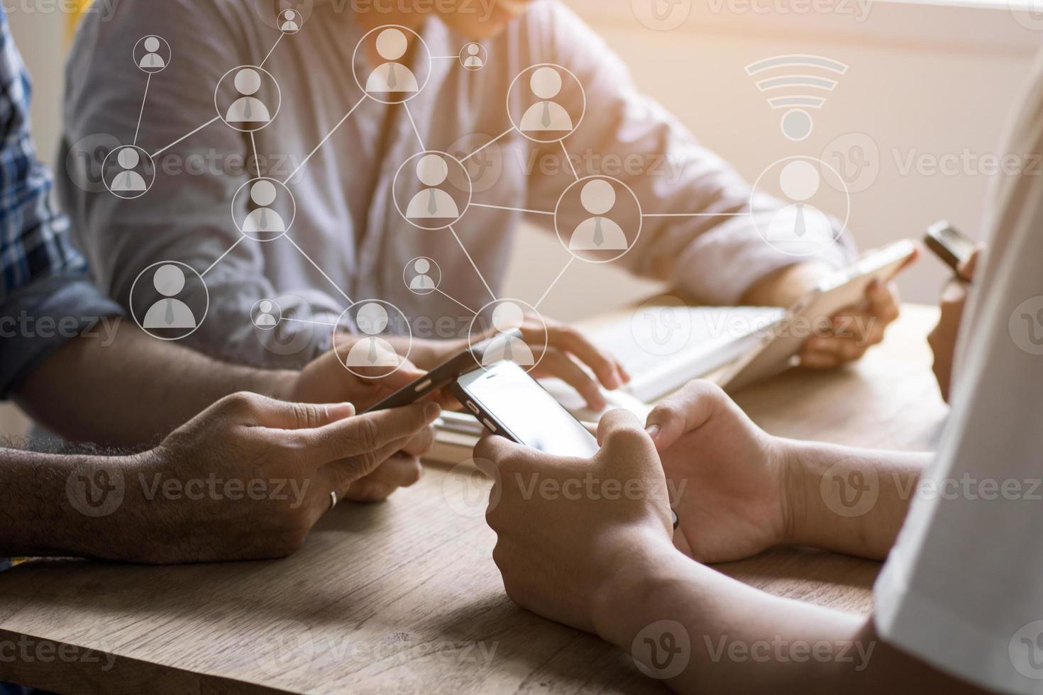 mensen die slimme telefoons gebruiken terwijl ze aan tafel zitten foto