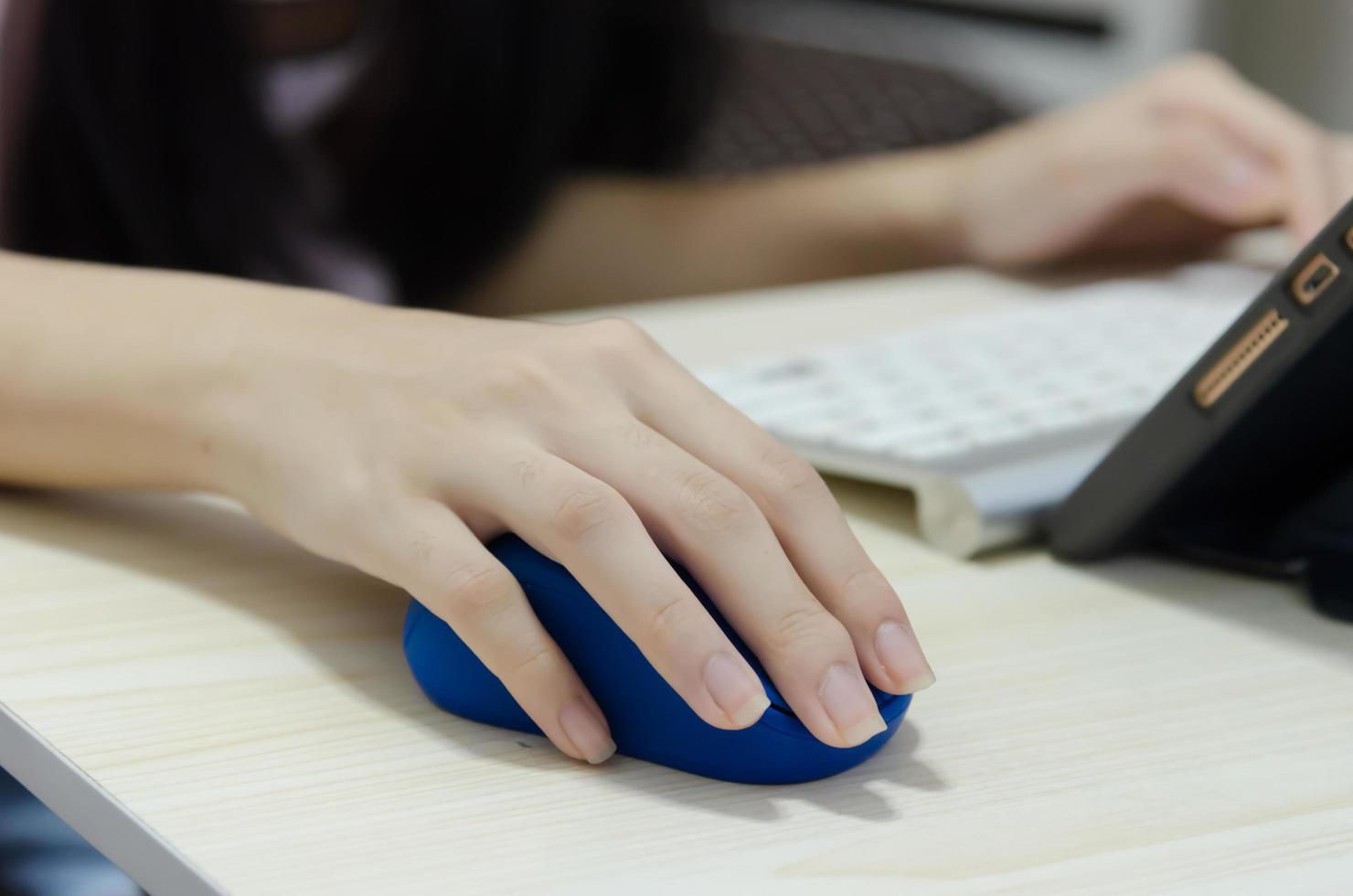 de hand van een meisje met een blauwe computermuis foto