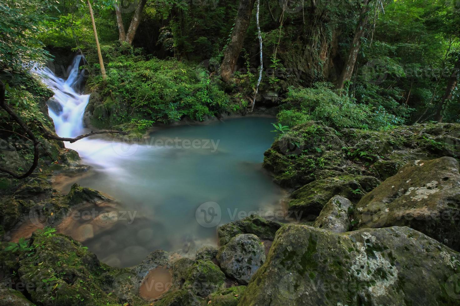 waterval op rotsen in bos foto