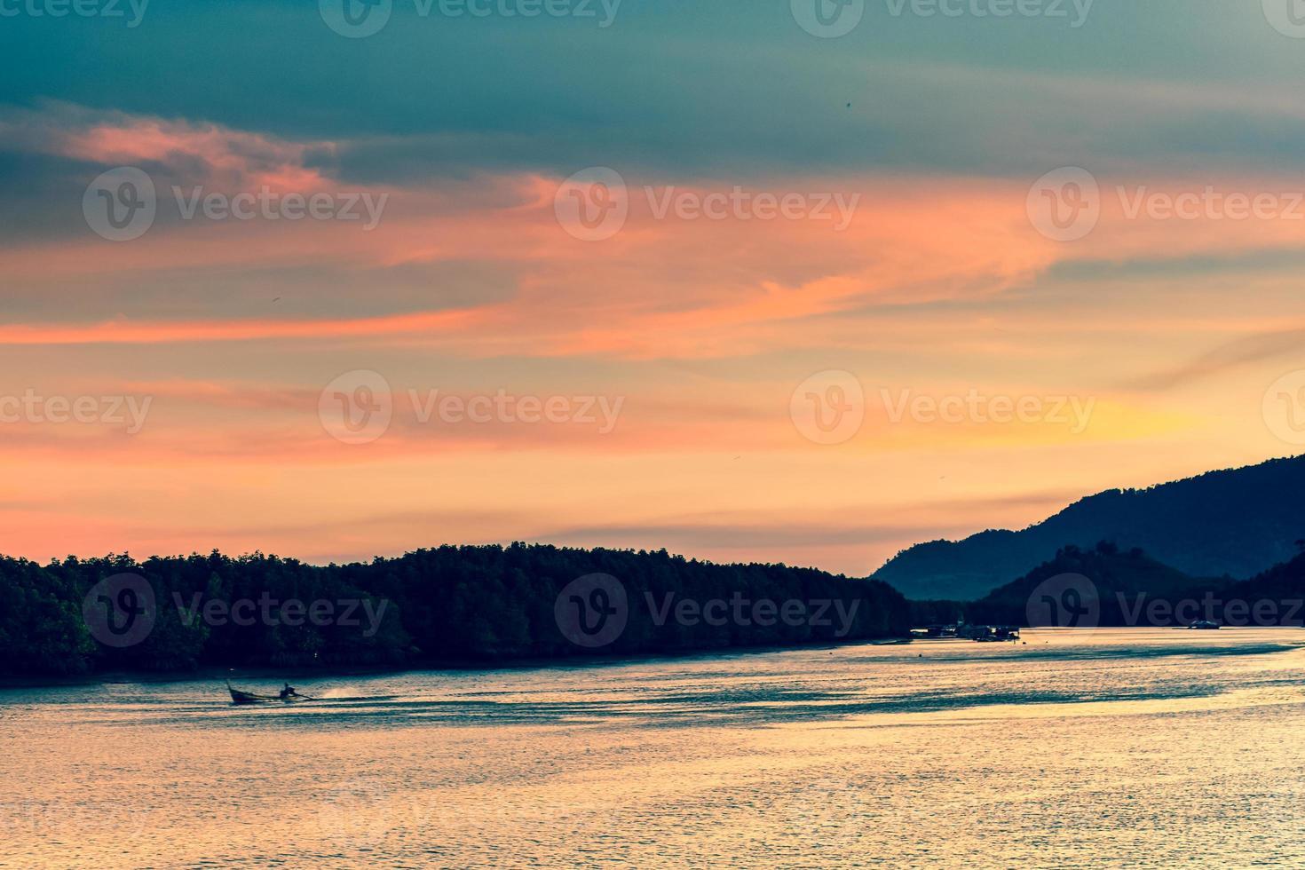 zonsondergang over een oceaan met bergen foto