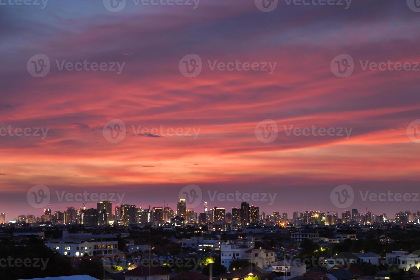 roze wolken boven een stad bij zonsondergang foto