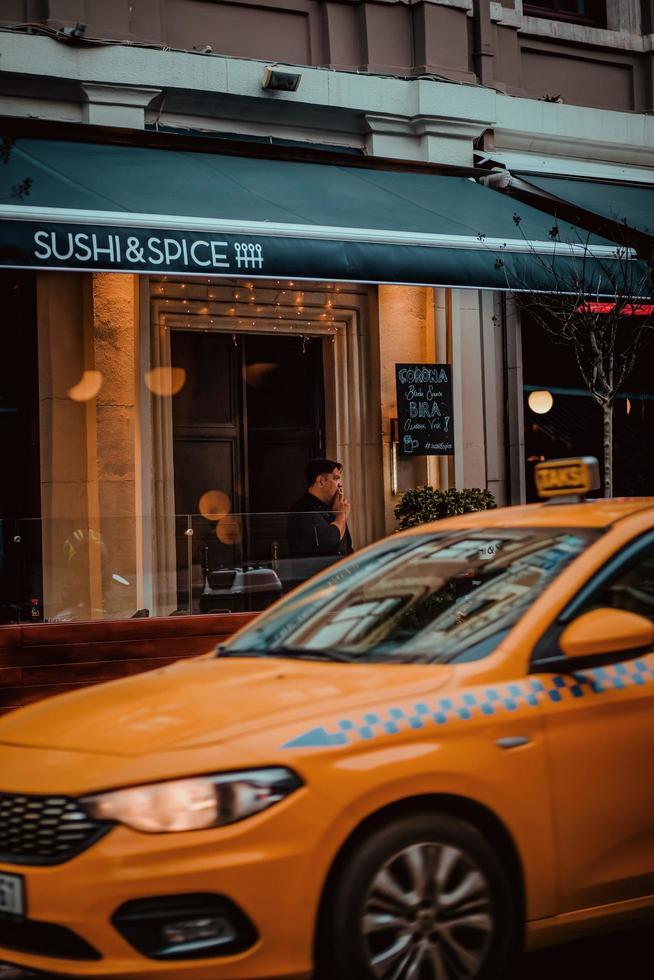 gele taxi langs sushi en kruidenrestaurant foto