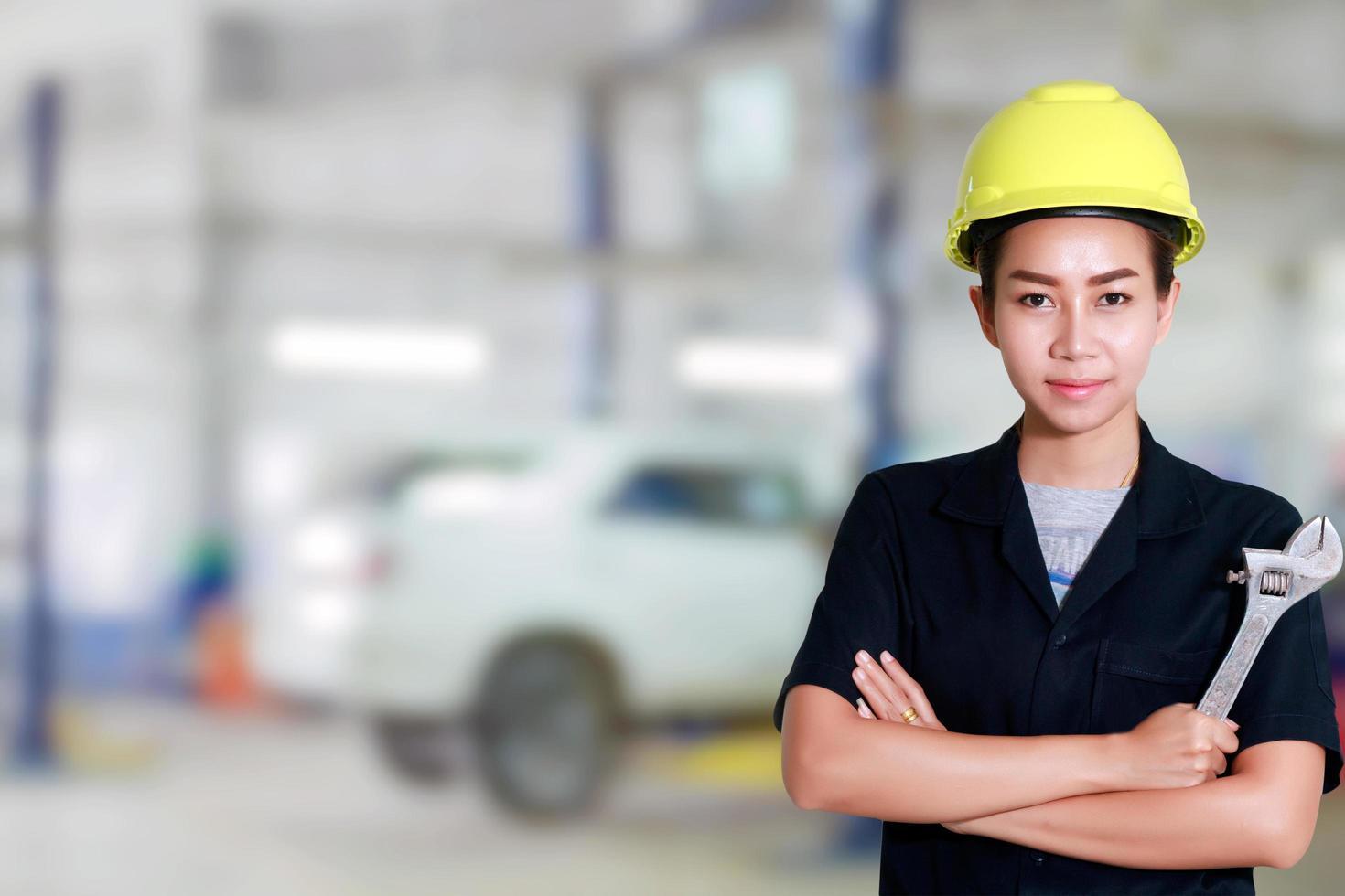 Aziatische vrouweningenieur die een moersleutel in de hand houdt foto