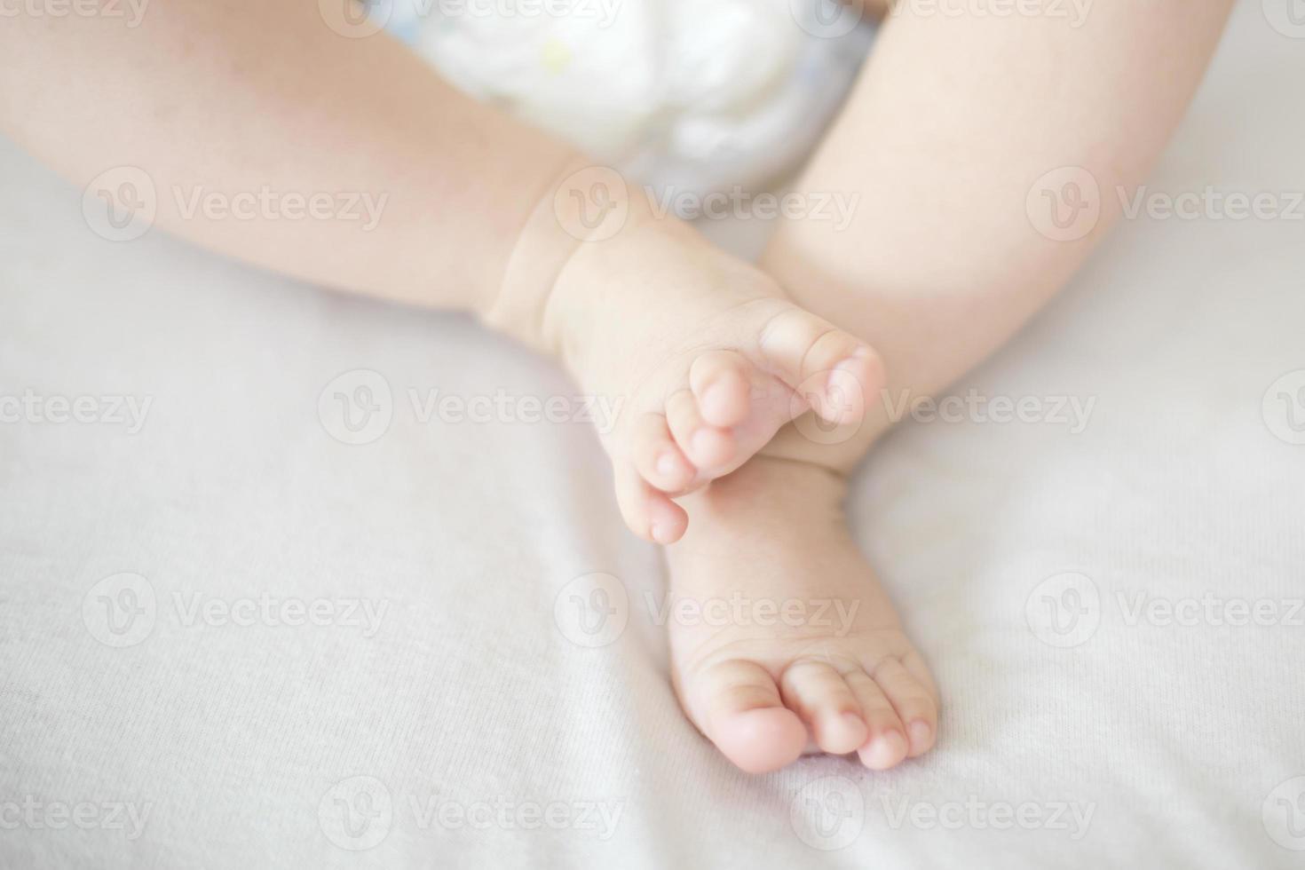 kleine babymeisje voeten op het bed foto