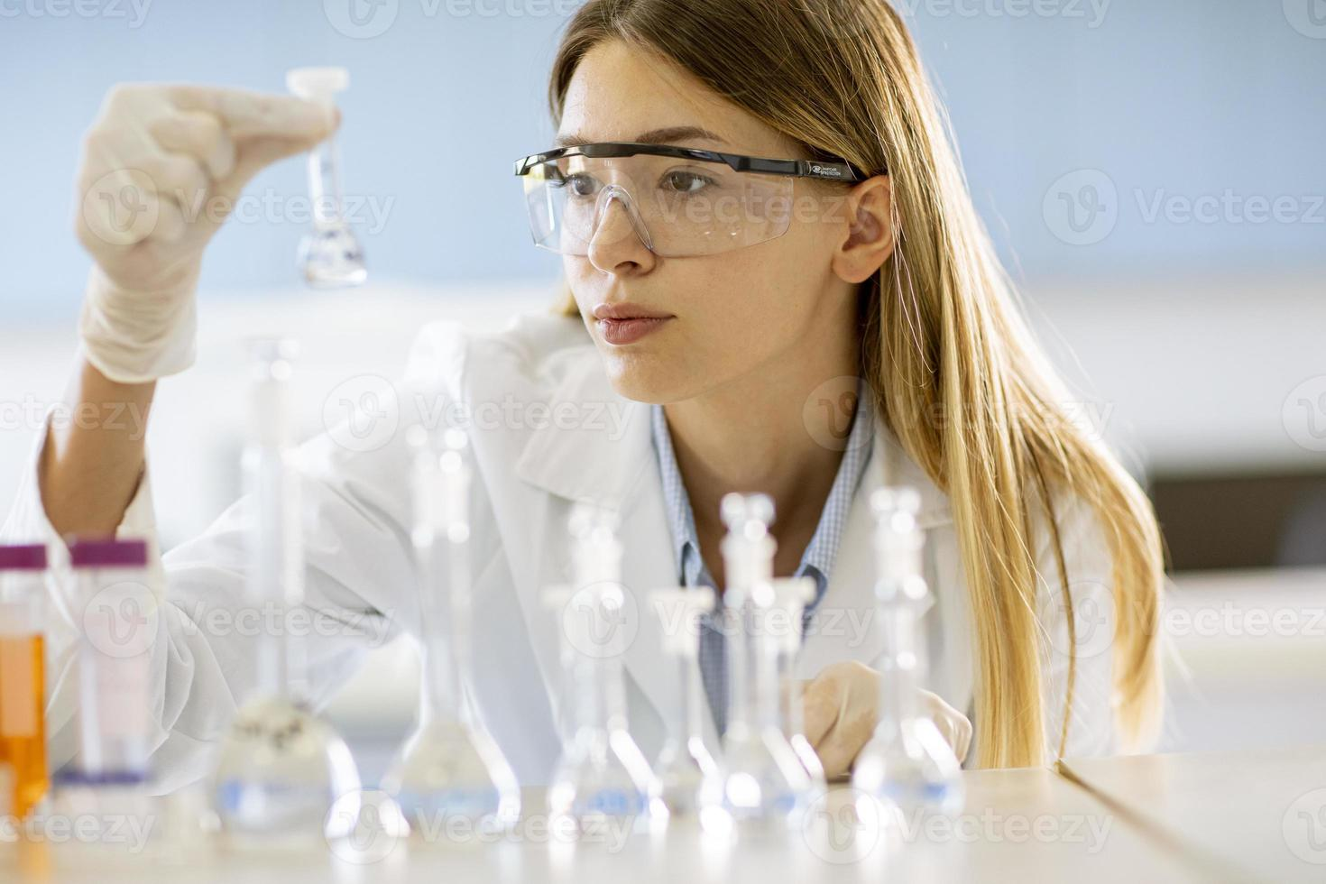 vrouwelijke medisch of wetenschappelijk onderzoeker kolven met oplossingen in een laboratorium kijken foto