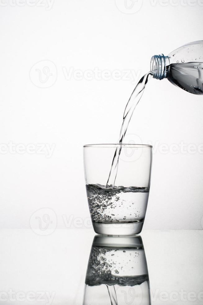 close-up van het gieten van water in glas geïsoleerd op een witte achtergrond foto