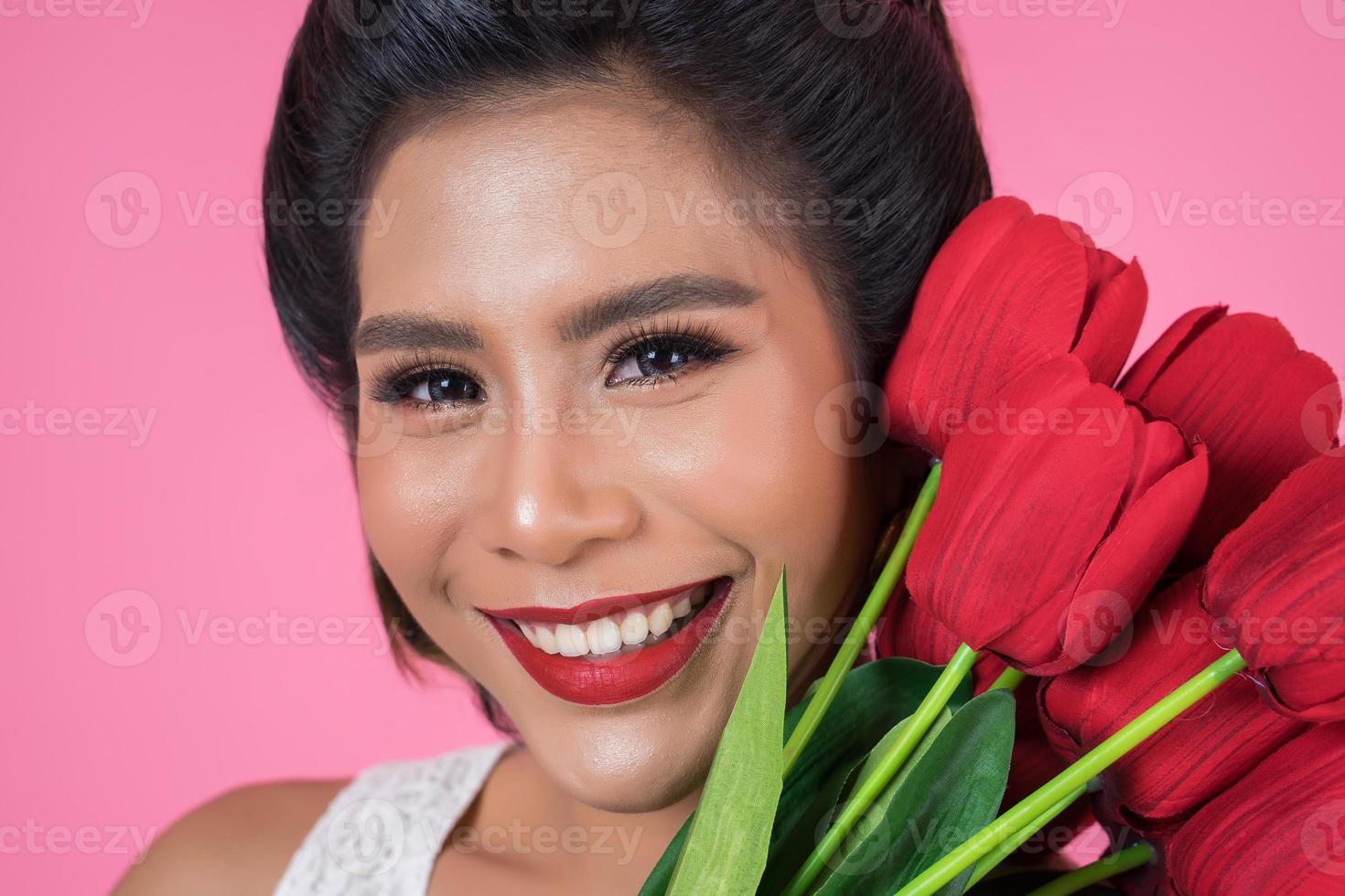 portret van een mooie vrouw met een boeket van rode tulp bloemen foto