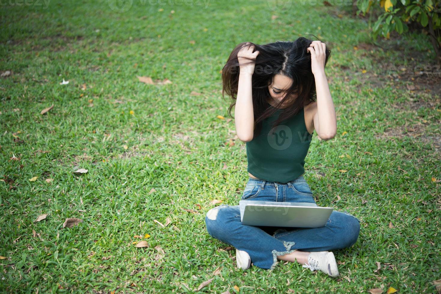 ernstige vrouw die op laptop buitenshuis werkt foto