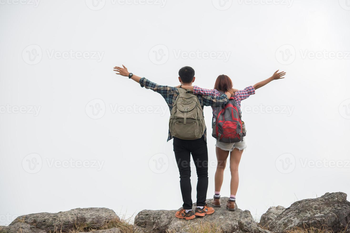 wandelaars met rugzakken die bovenop een berg staan en genieten van uitzicht op de natuur foto