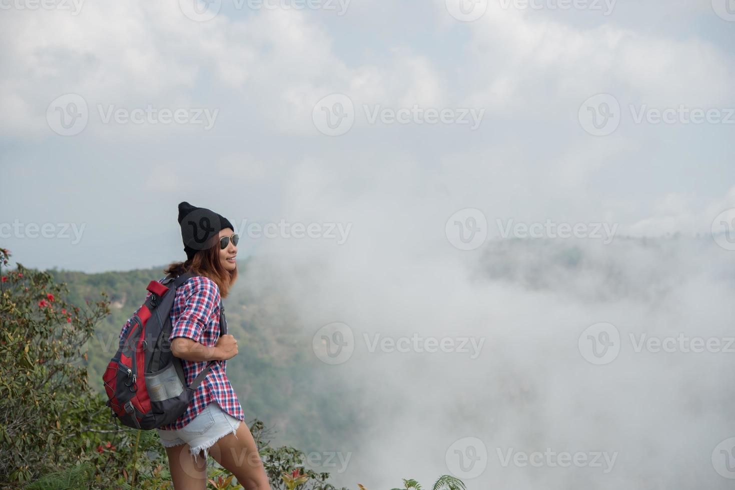 wandelaar met rugzak staande op de top van een berg en genietend van uitzicht op de natuur foto