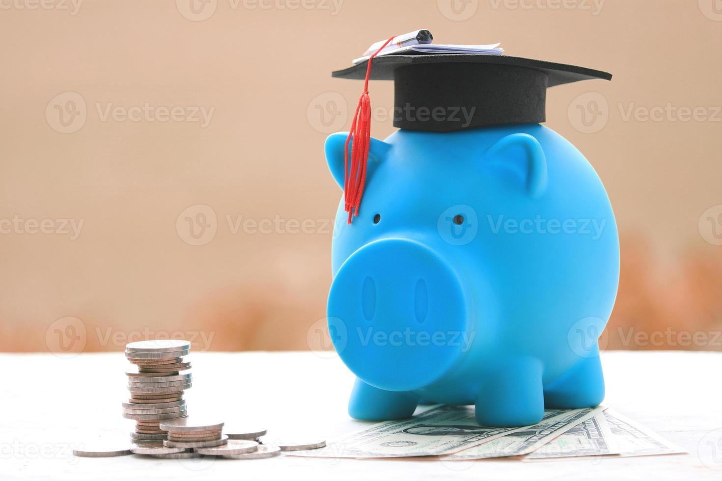 stapels munten naast blauwe spaarvarken met een baret foto