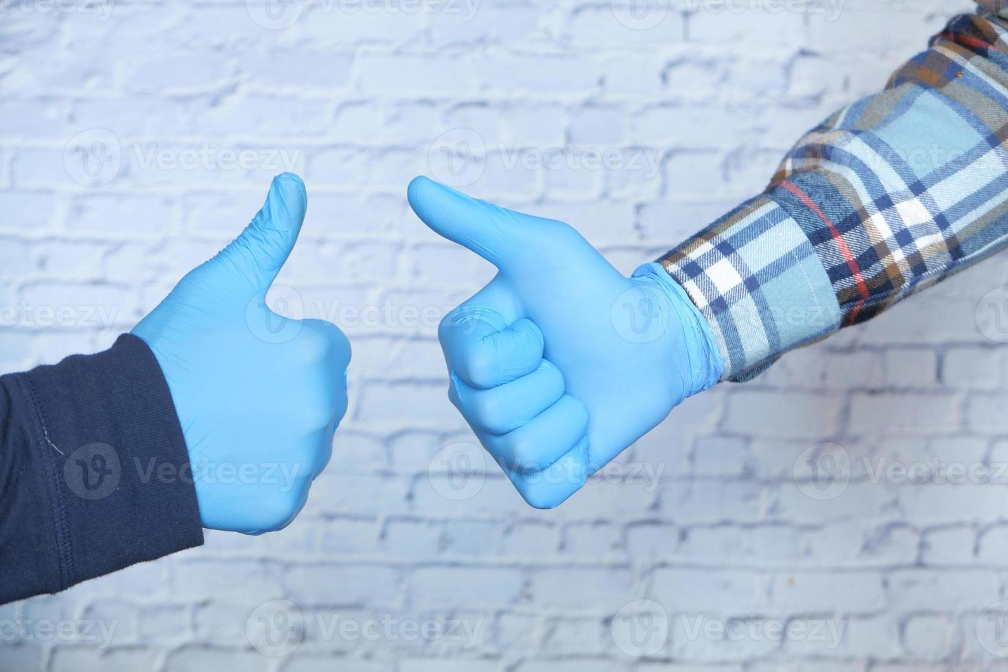 close-up van twee mensen die medische handschoenen dragen die een duim omhoog ondertekenen foto