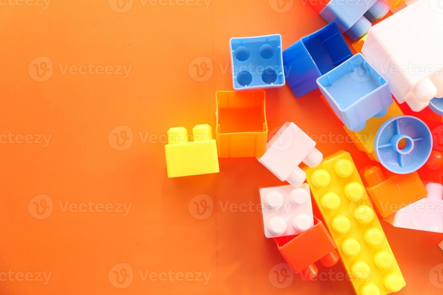 kleurrijke bouwstenen op oranje tafel, close-up foto