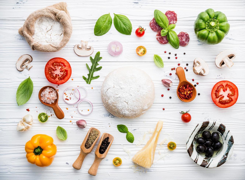 verse ingrediënten voor pizza op armoedig wit hout foto