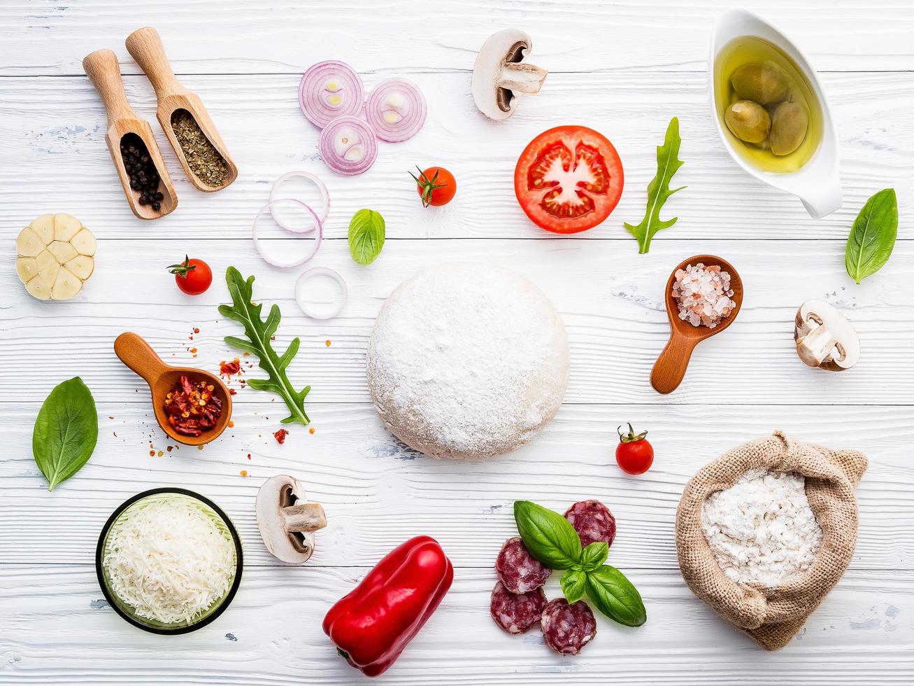 pizzadeeg en ingrediënten op een armoedige witte achtergrond foto