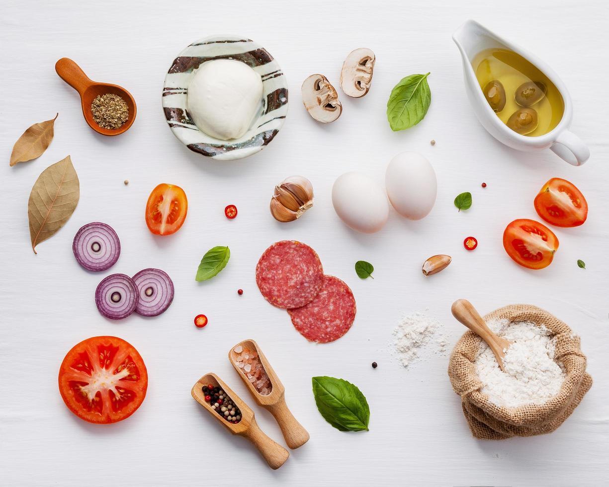 ingrediënten voor pizza op armoedige witte houten achtergrond foto