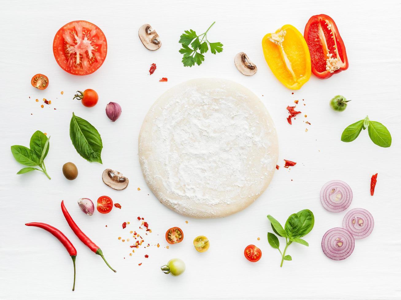 pizzadeeg en ingrediënten op wit foto