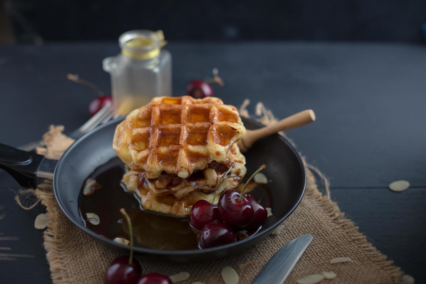 honing op wafels in een pan met kersen op donkere houten tafel foto