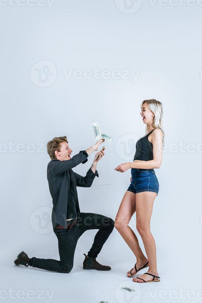 gelukkig paar dat dollarbankbiljetten toont foto