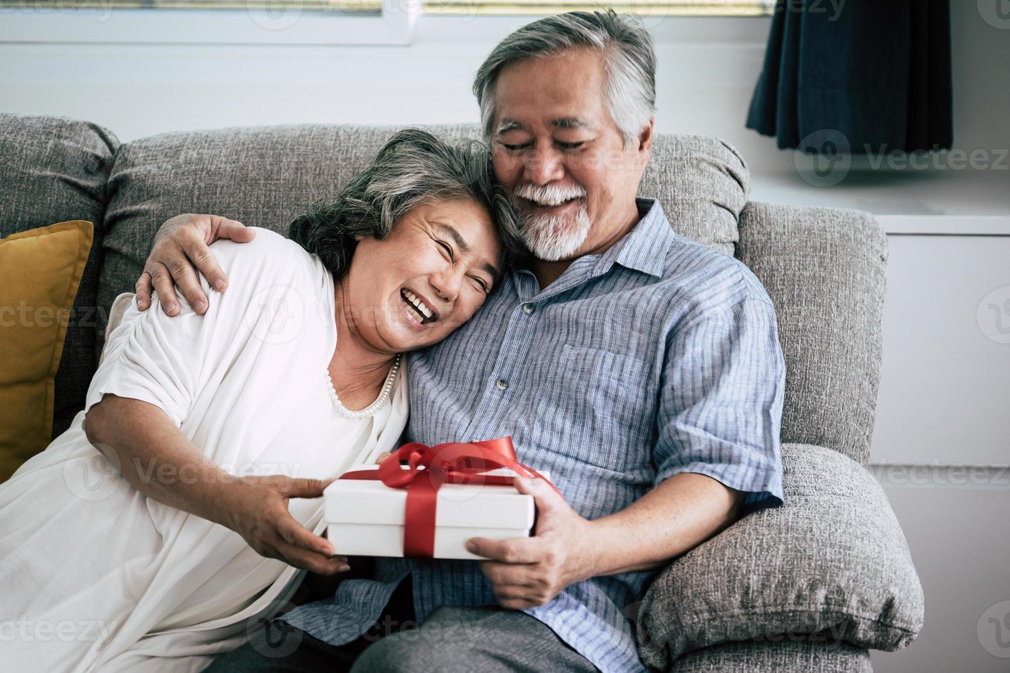 bejaarde echtpaar verrast met geschenkdoos in de woonkamer foto