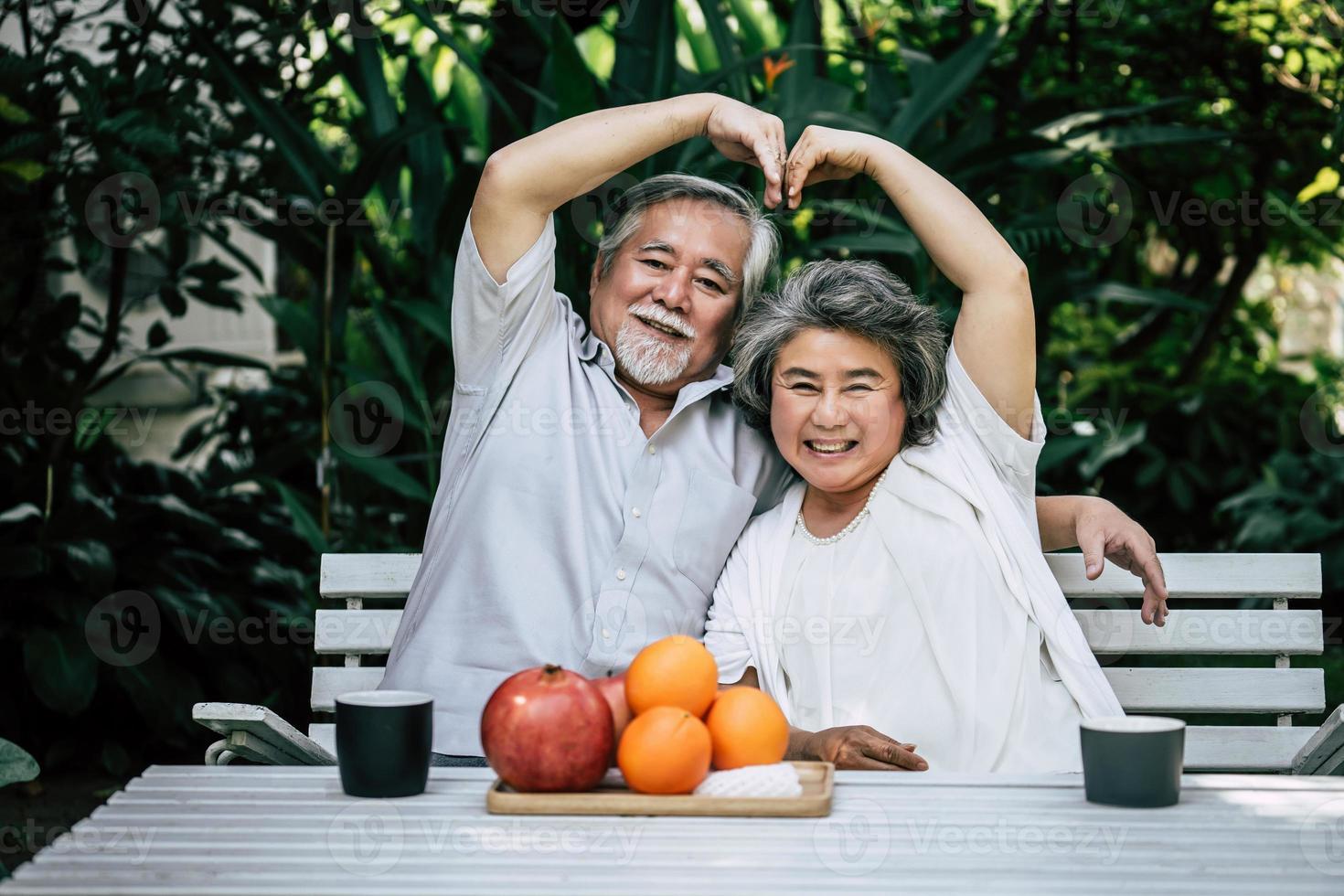 bejaarde echtpaar spelen en eten wat fruit foto