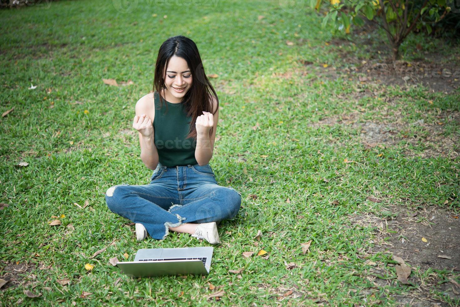 jonge mooie vrouw zittend op het groene gras en met behulp van laptop in het park foto