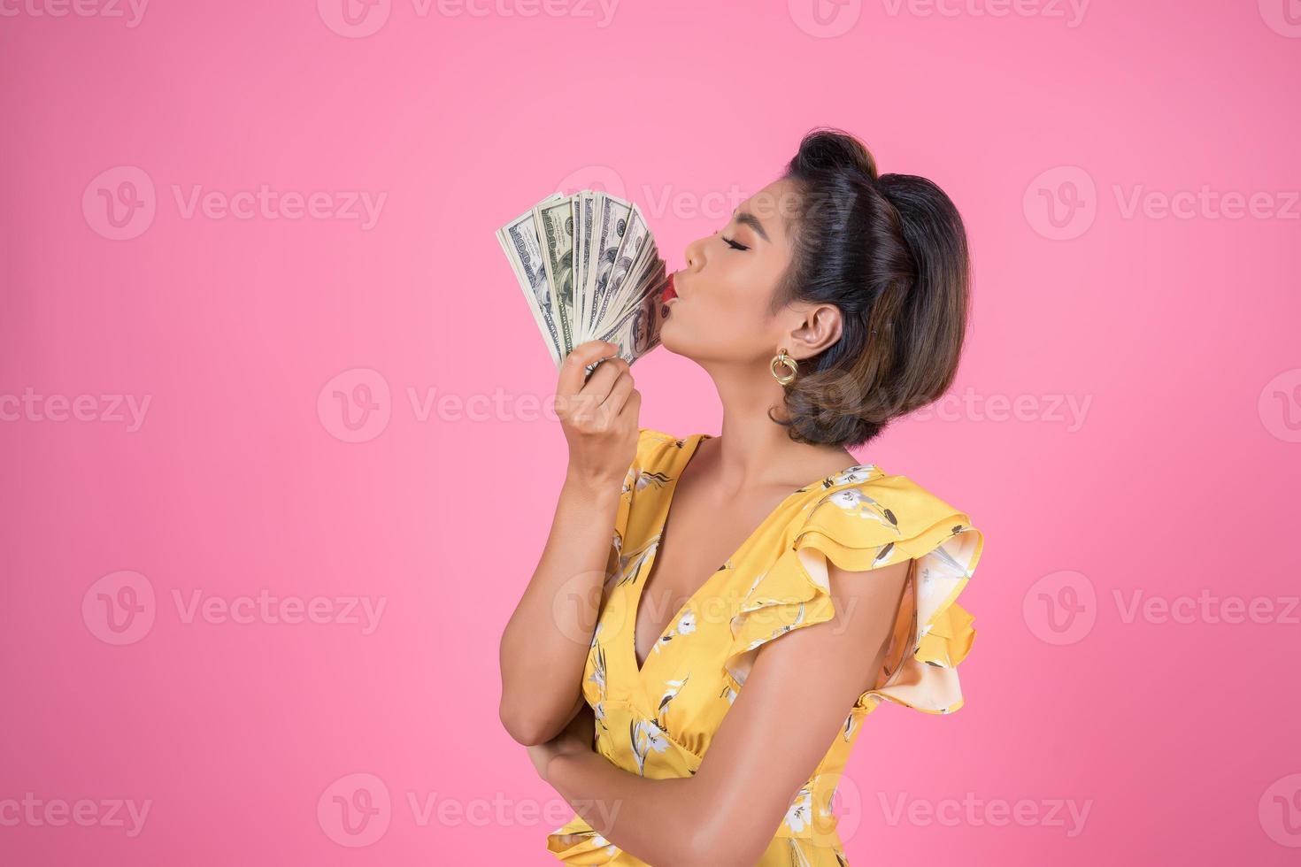 gelukkig modieuze vrouw met geld om te winkelen foto