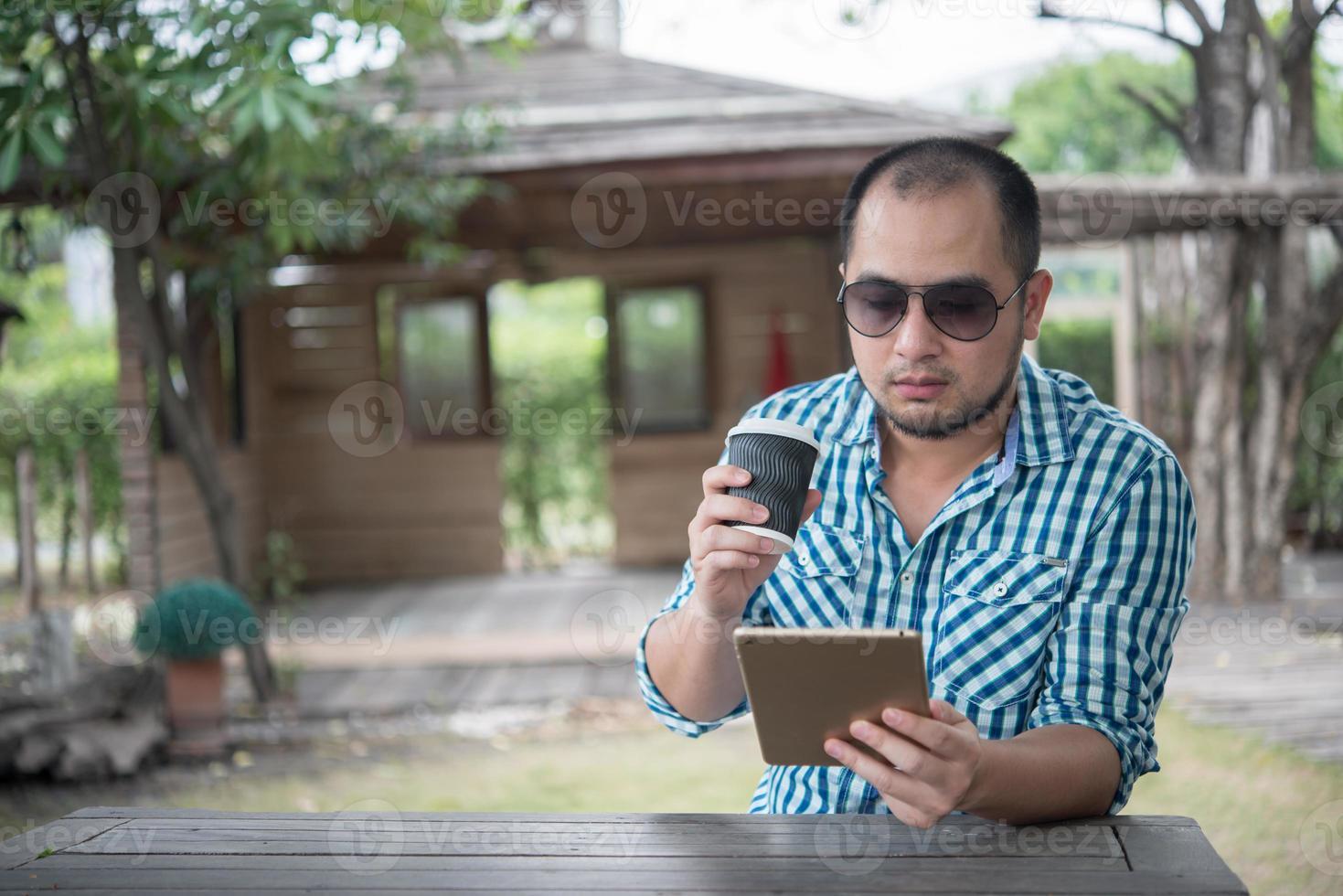jonge man zit buiten aan een houten tafel en ontspannen met tablet foto
