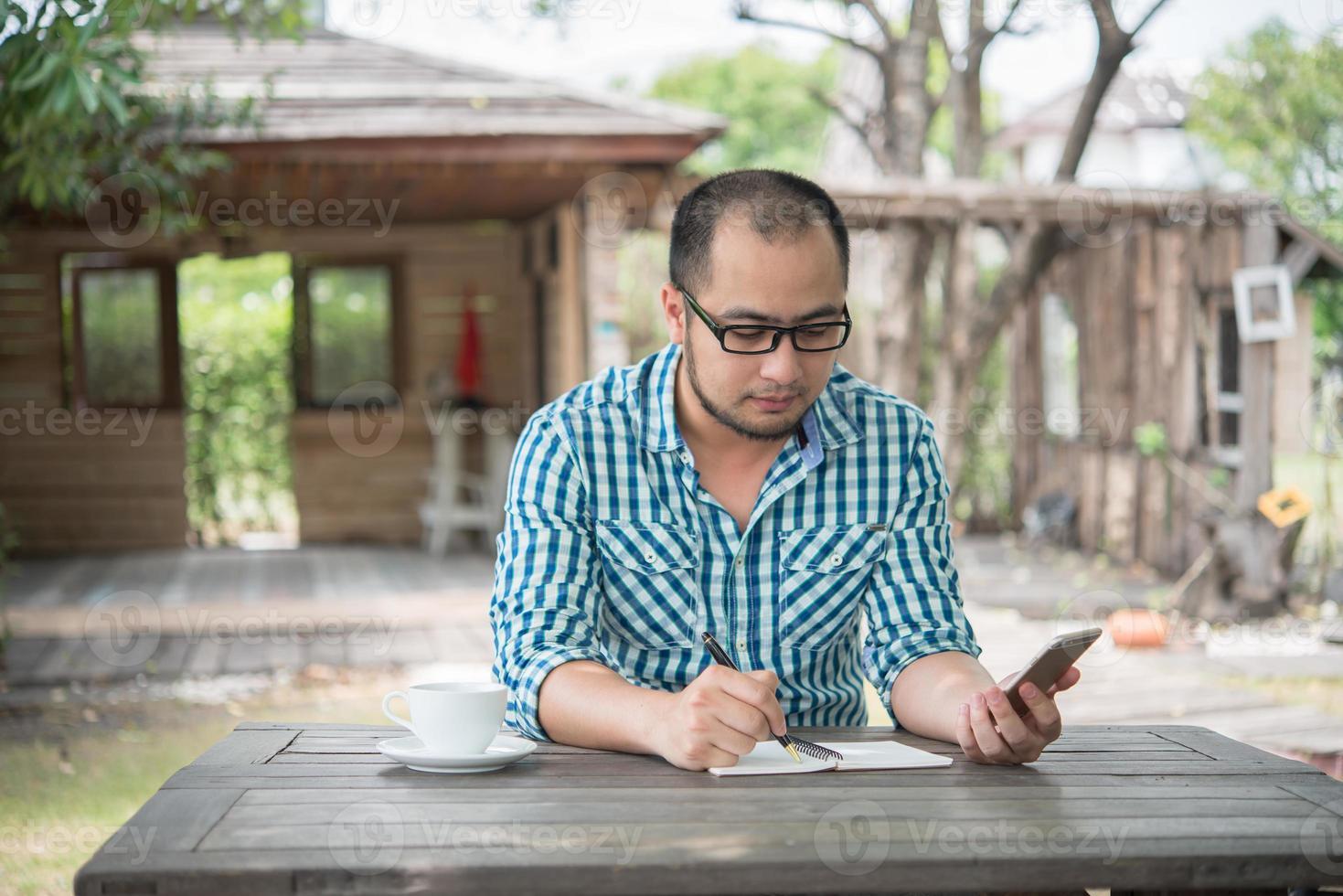 jonge zakenman met behulp van smartphone tijdens het werken in de tuin foto