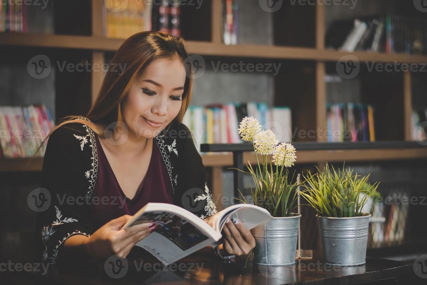 gelukkig zakenvrouw lezen van een boek terwijl u ontspant in café foto