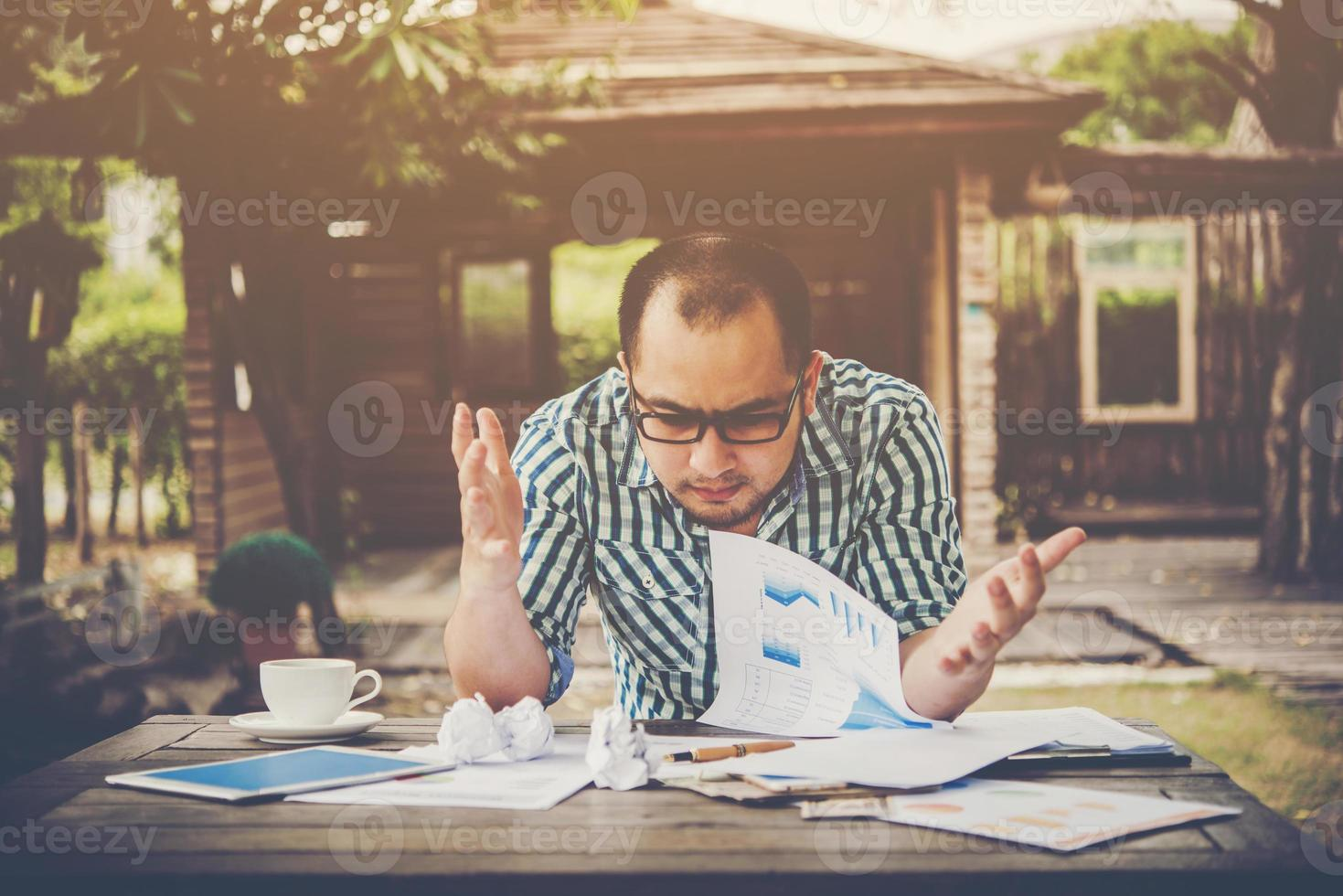benadrukt zakenman met papieren en grafieken om thuis aan tafel te zitten foto