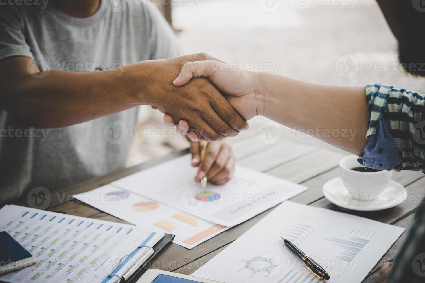 close-up van twee zakenmensen handen schudden zittend op de werkplek foto