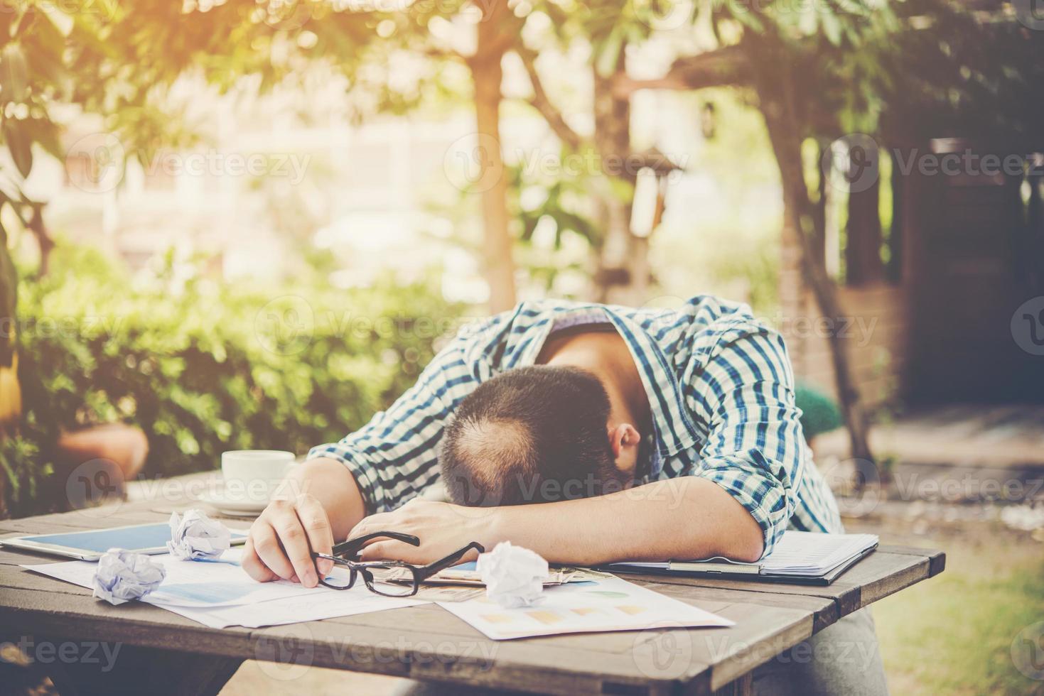 moe werkende man slapen op de werkplek vol werk foto