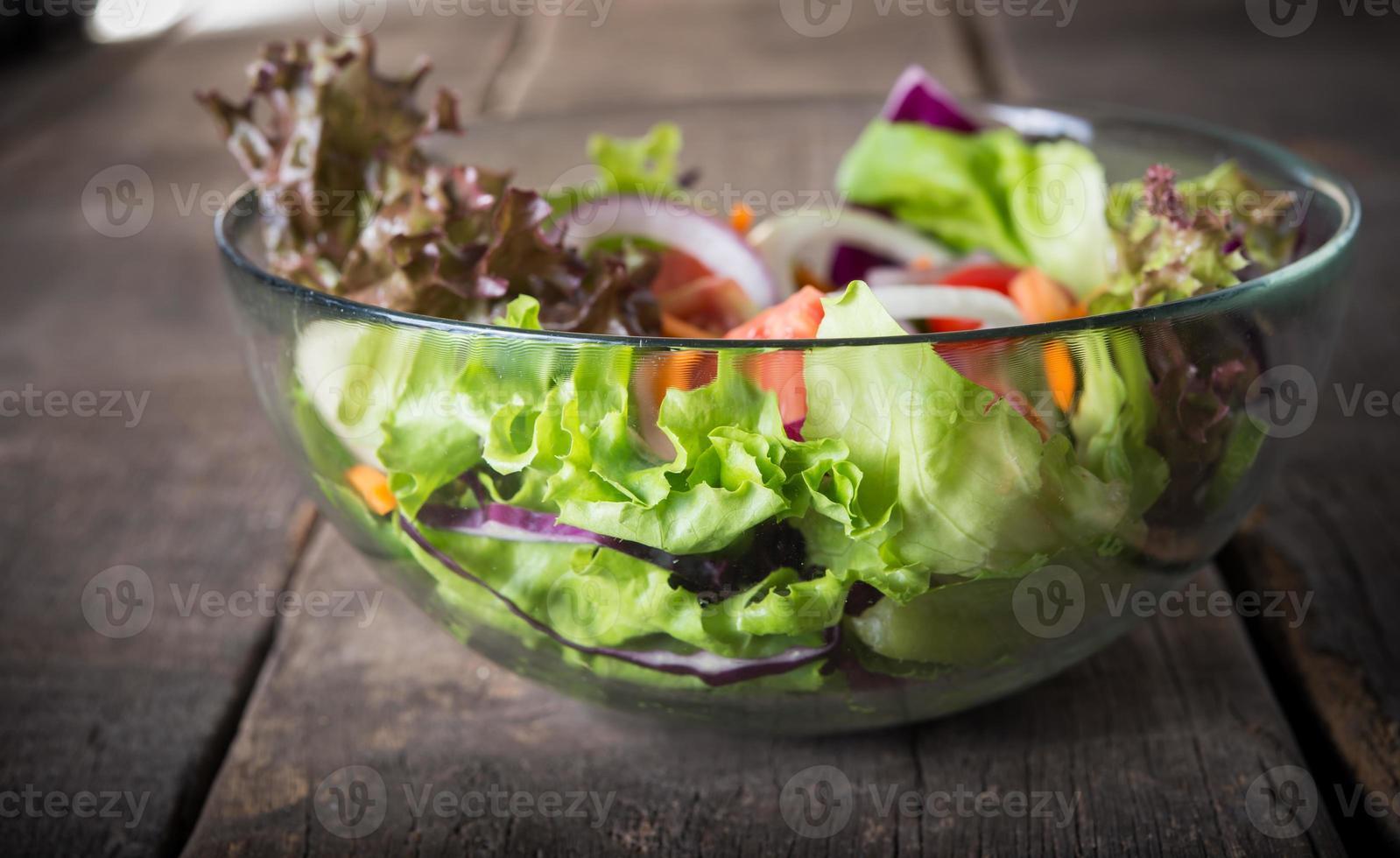 verse groentesalade in glazen kom op houten achtergrond foto