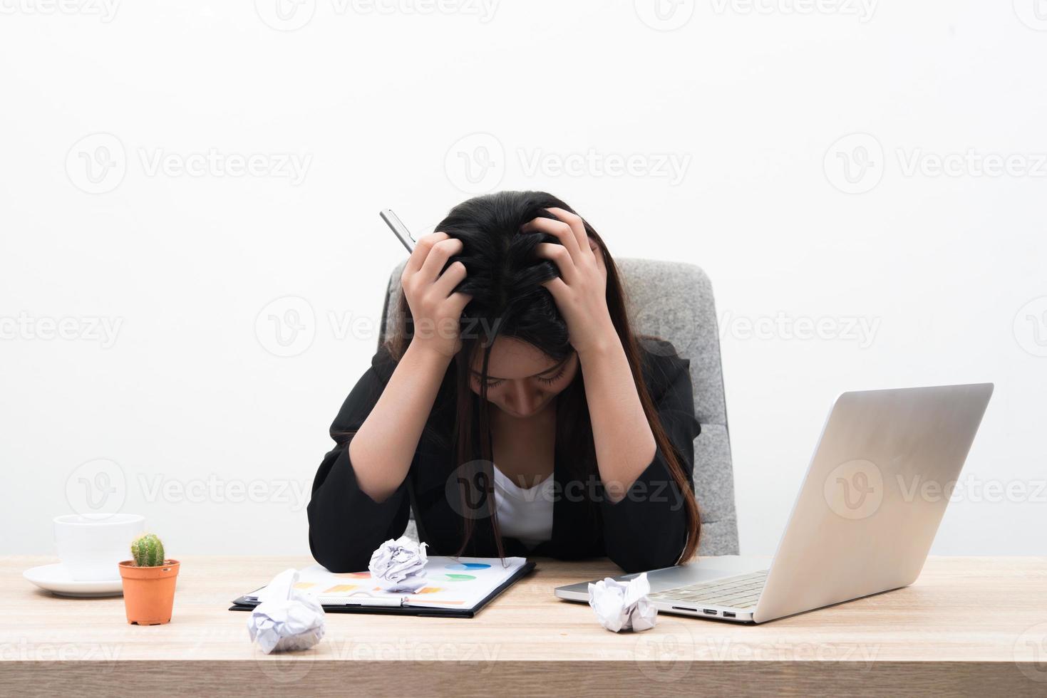 jonge zakenvrouw houdt haar hoofd vast en ziet er stressvol uit op een witte achtergrond foto