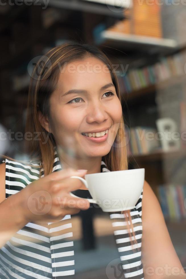 Aziatische vrouw ontspannen met koffie in café foto