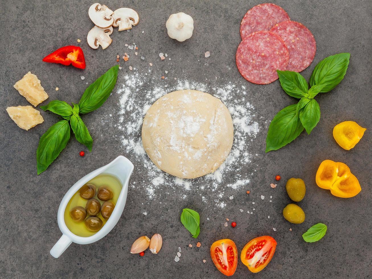 pizzadeeg en ingrediënten op een donkere achtergrond foto