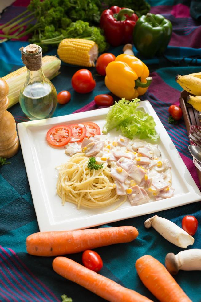 pasta carbonara met spek en Parmezaanse kaas op een witte plaat met groenten op kleurrijk tafelkleed foto
