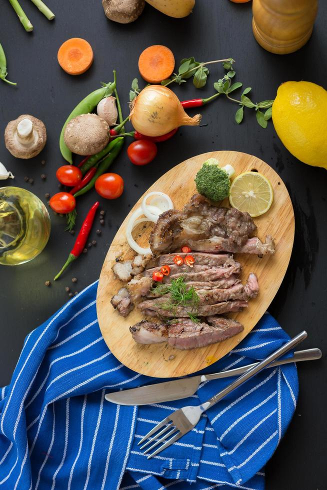 Gegrilde steak en garnituren op houten snijplank met uien, chilipepers, tomaten, sperziebonen en een citroen op donkere houten tafel foto
