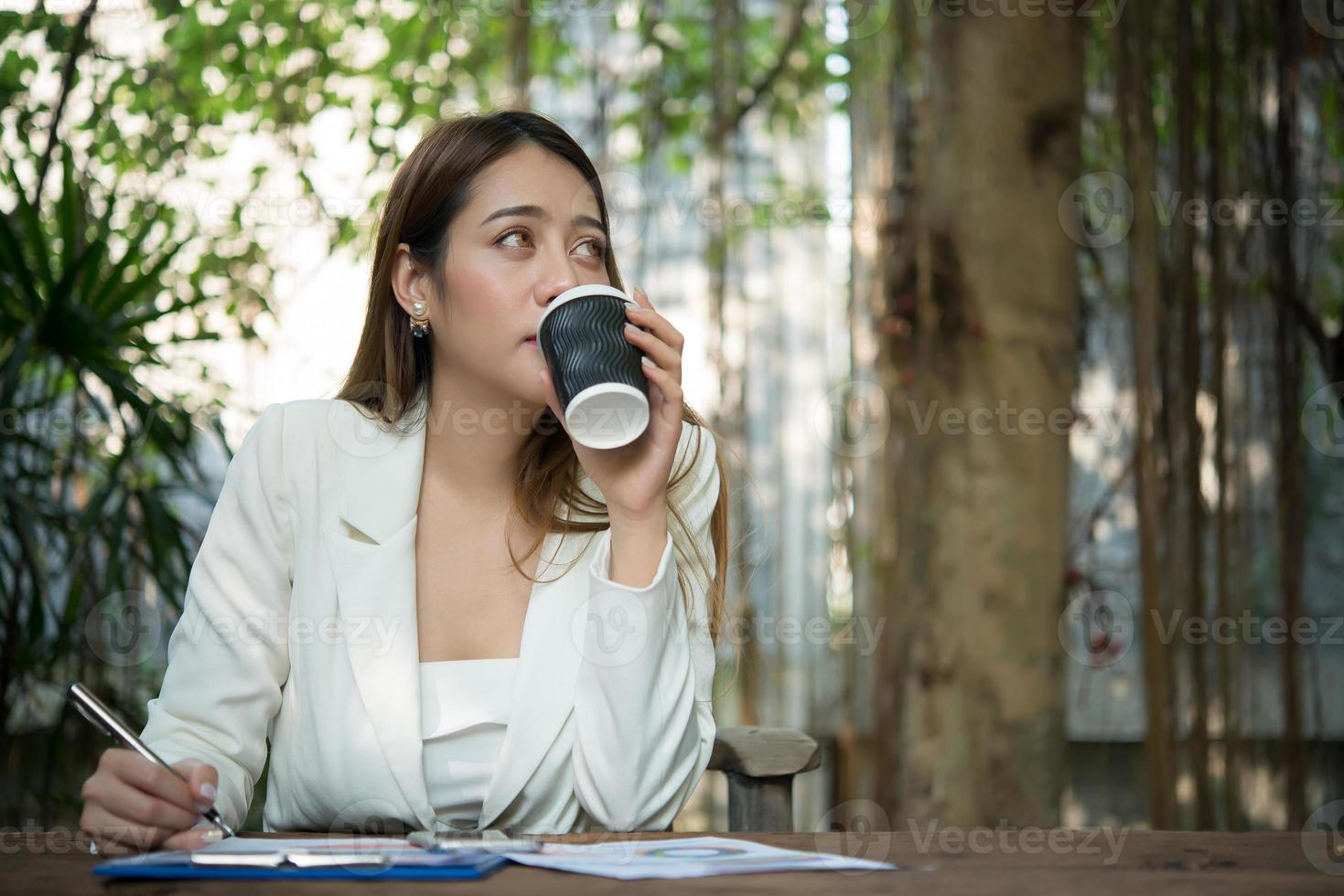 jonge zakenvrouw zitten in een kantoor een kopje koffie drinken foto