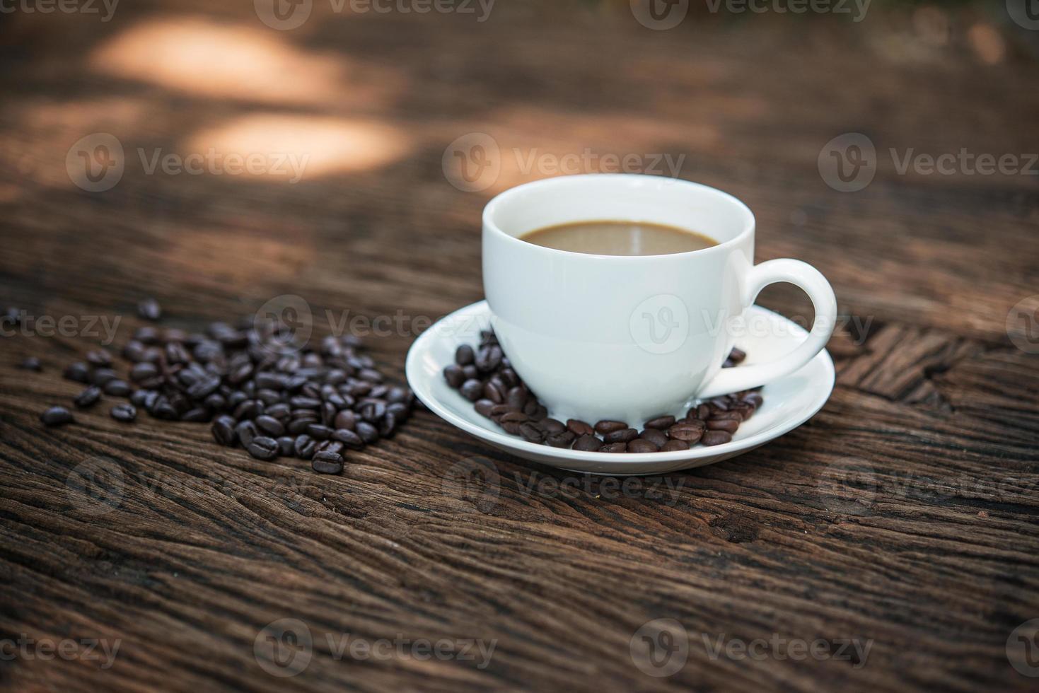 koffiekopje en koffiebonen op houten tafel foto