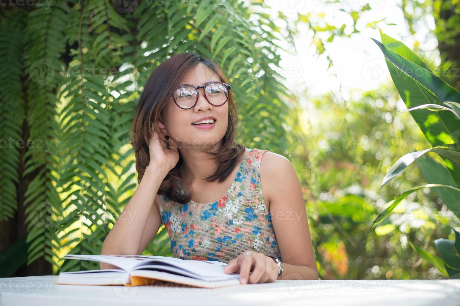 jonge hipster vrouw lezen van boeken in eigen tuin met de natuur foto