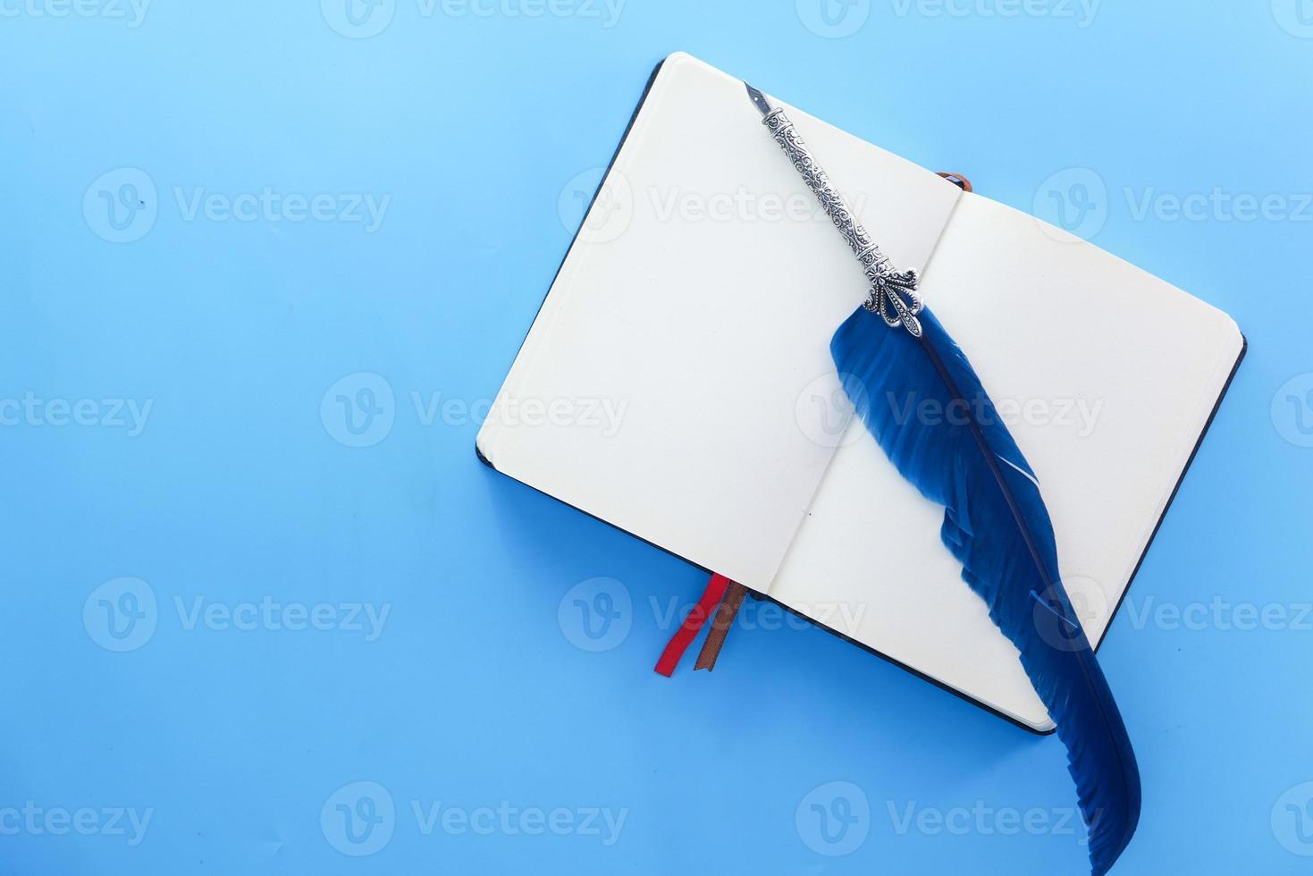 open boek en oude vulpen op blauwe achtergrond foto