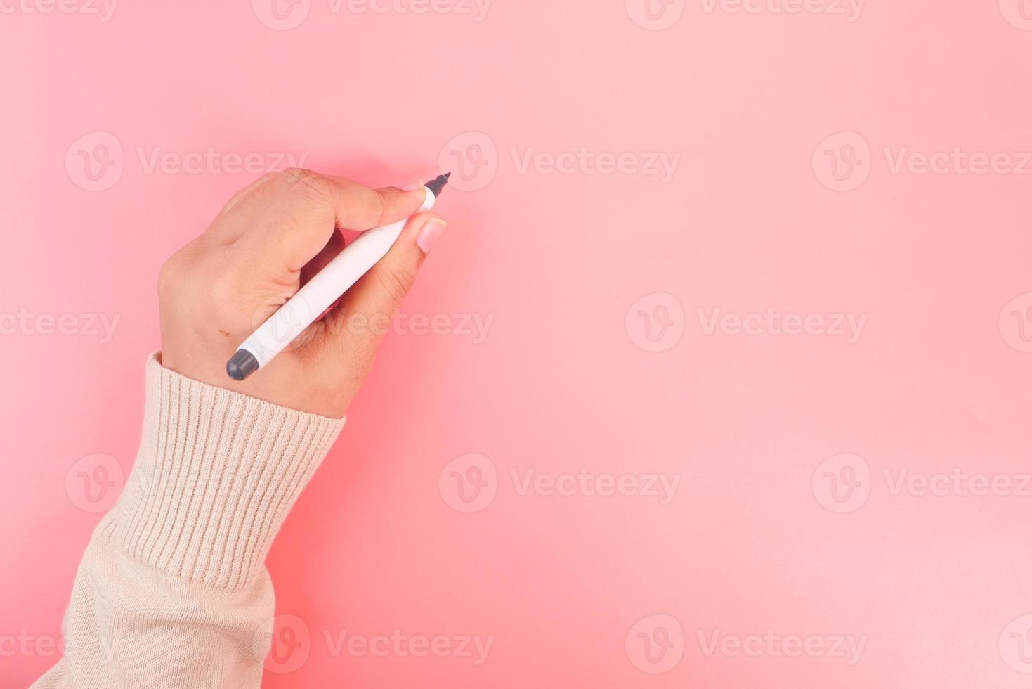 vrouwen die met pen op roze achtergrond schrijven foto
