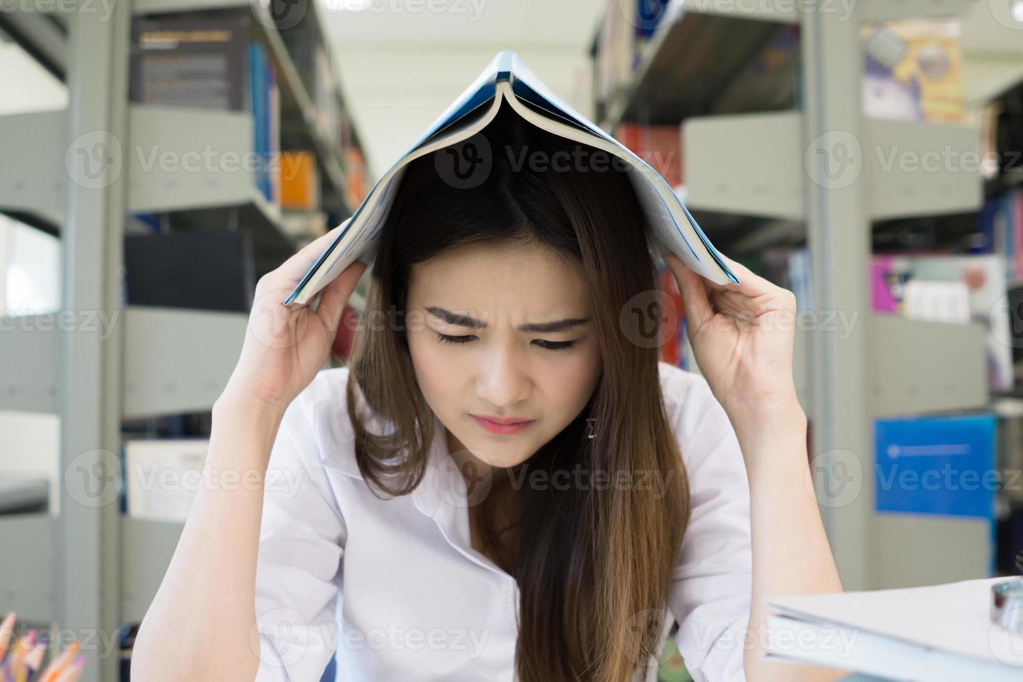 portret van student die haar hoofd bedekt met een boek tijdens het lezen foto
