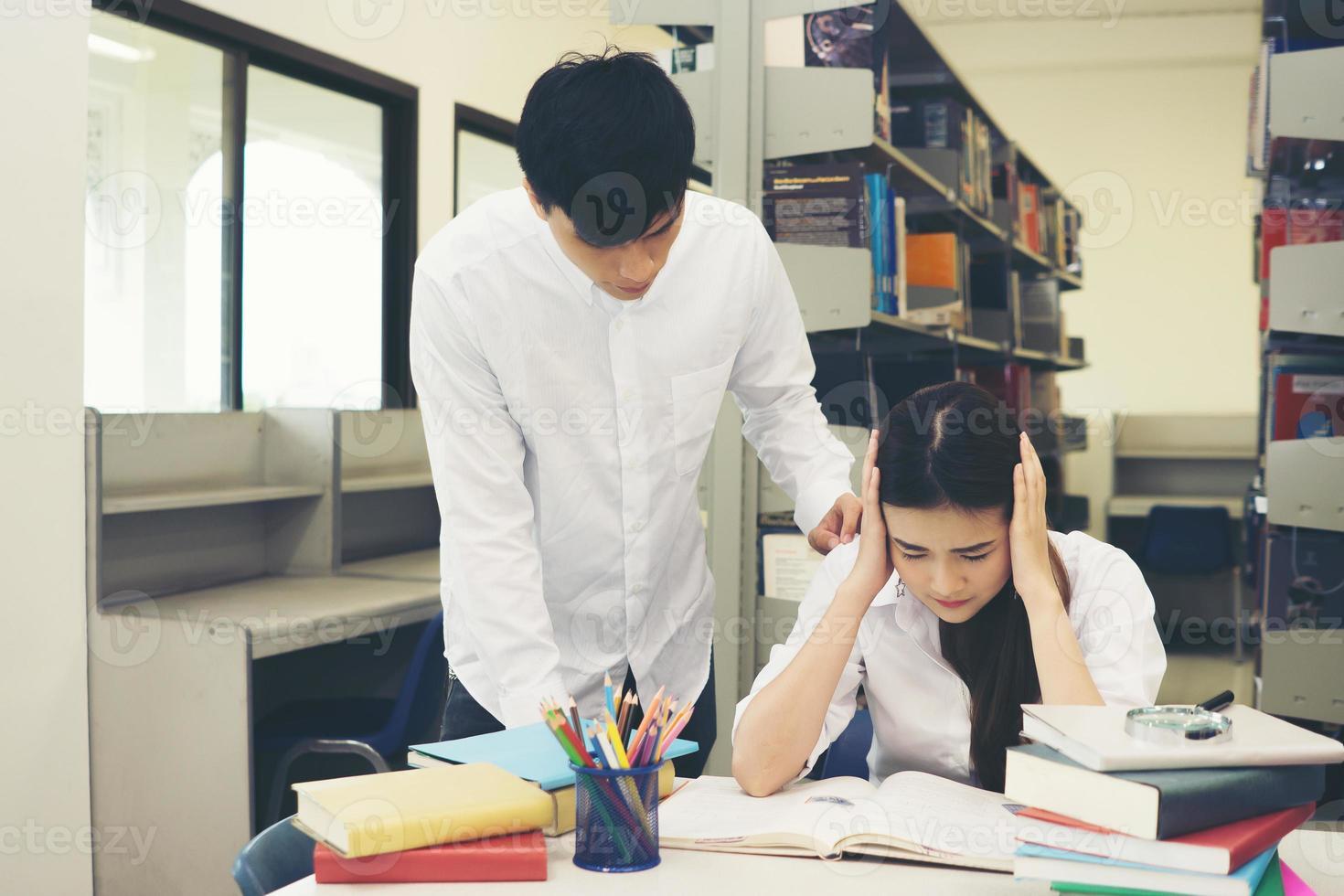 portret van de student haar hoofd aan te raken tijdens het lezen van een boek in de universiteitsbibliotheek foto